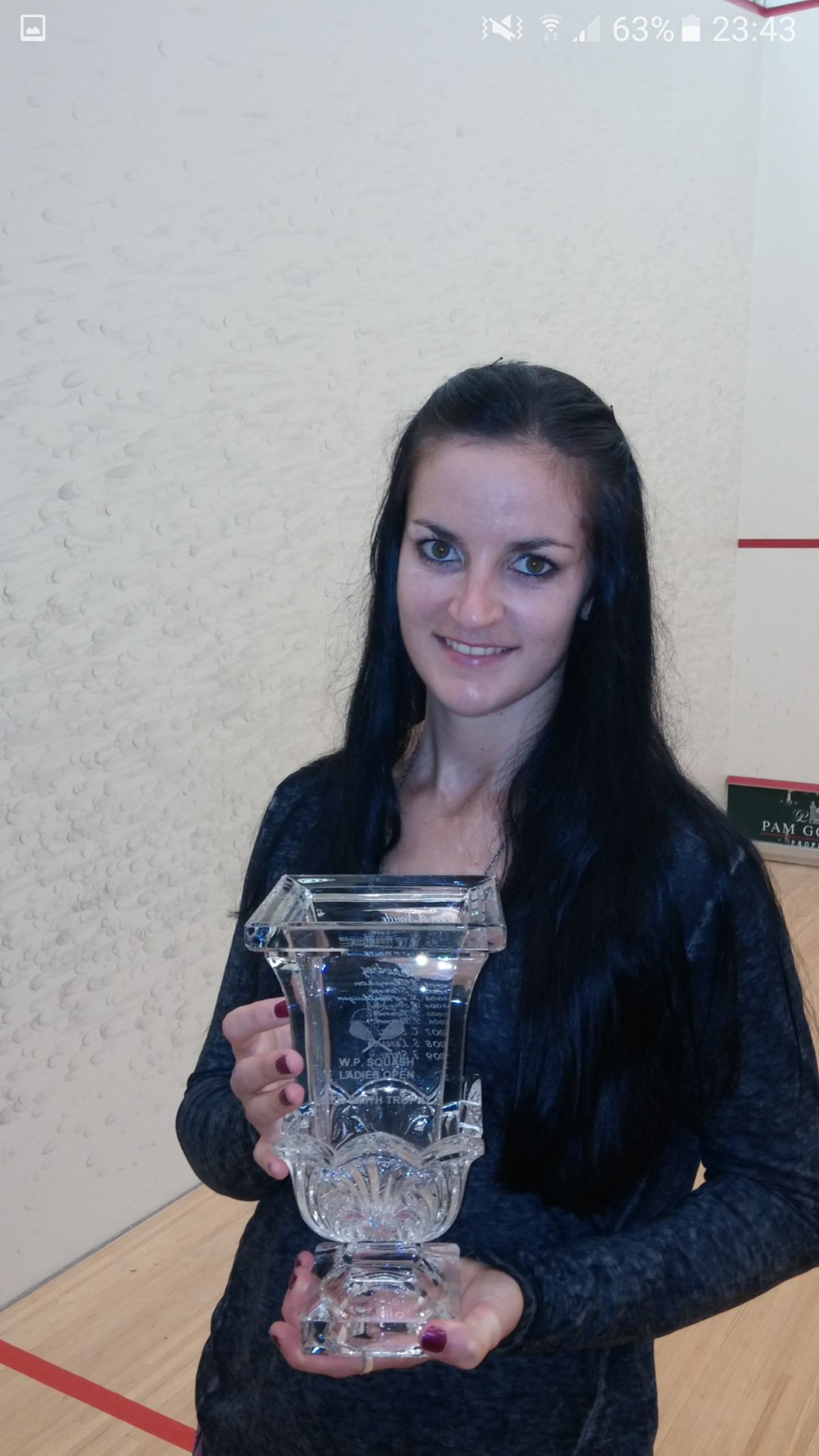 Milnay posing with trophy on squash court