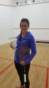 Milnay posing with racket and trophy on squash court